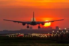 Flugzeug landet während des Sonnenaufgangs Stockfotos