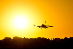Flugzeug-Landung während des Sonnenuntergangs Stockfotografie