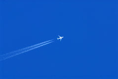Flugzeug mit Dampf schleppt in einem blauen Himmel Stockfotografie
