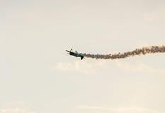 Flugzeug mit farbigem Spurnrauchfliegen im Blau bewölkt, des Sonnenuntergangs und der Sonne Strahlen des Himmels, aerobatic der S Lizenzfreie Stockfotos
