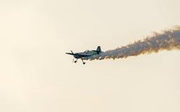 Flugzeug mit farbigem Spurnrauchfliegen im Blau bewölkt, des Sonnenuntergangs und der Sonne Strahlen des Himmels, aerobatic der S Stockfotos