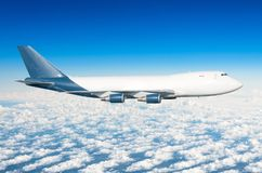 Flugzeug mit vier Maschinen, LKW ohne Öffnungen im Himmel über der Höhe der Wolkenflugreise-Sonne lizenzfreie stockbilder