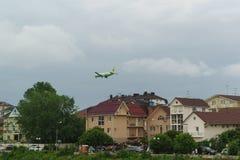 Flugzeug S7 fliegt niedrig über die Häuser im Erholungsortdorf von Adler Bewölkter Tag im Frühsommer Stockfotografie