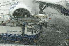 Flugzeug und enteisenauto am Schneesturm Lizenzfreies Stockbild