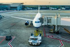 Flugzeug- und Flughafenservice-Fahrzeuge nahe dem Anschluss bei Sonnenuntergang, Feiertagskonzept stockfotos