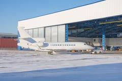 Flugzeug wird nach innen über Schleppseiltraktor der Luftfahrthangar für Wartung geliefert stockbild