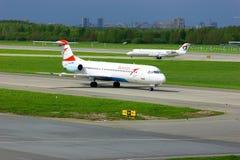 Flugzeuge Austrian Airlines Fokker 100 und Severstal Canadair CRJ-200 in internationalem Flughafen Pulkovo in St Petersburg, Russ Lizenzfreie Stockfotografie