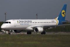 Flugzeuge Ukraine International Airliness Embraer ERJ190-100, die für Start von der Rollbahn sich vorbereiten Stockfotos