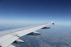 Flugzeugflügel, der über Land fliegt Stockbild