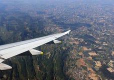 Flugzeugflügel, der über Land fliegt Lizenzfreie Stockbilder