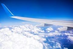 Flugzeugflügel mit blauem Himmel und weißen Wolken Stockfoto