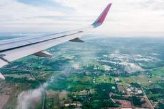 Flugzeugflügel während des Fluges, angesehen vom Passagierfenster dort sind viele weißen Wolken im blauen Himmel über dem Boden, lizenzfreies stockfoto