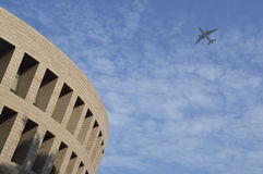 Flugzeugfliege über dem modernen Gebäude. Stockbild