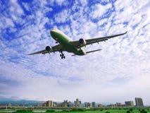 Flugzeugfliege über Gebäuden stockfotografie