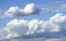 Flugzeugfliege durch blauen Himmel und weiße Kumuluswolke Stockbilder