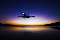Flugzeugfliegen auf buntem Abendhimmel über Meer bei Sonnenuntergang mit Stockbild