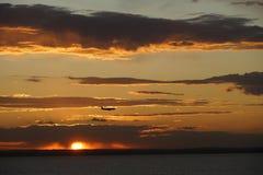 Flugzeugfliegen durch Sonnenuntergang Lizenzfreies Stockfoto