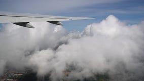 Flugzeugfliegen durch Wolken über der Stadt, flacher Flügelabschluß oben stock footage