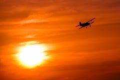 Flugzeugfliegen im goldenen Sonnenuntergang Lizenzfreie Stockfotos