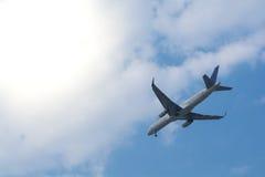 Flugzeugfliegen im Himmel und in der Sonne Lizenzfreies Stockfoto
