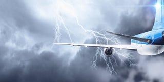 Flugzeugfliegen im stürmischen Himmel Gemischte Medien Stockbilder