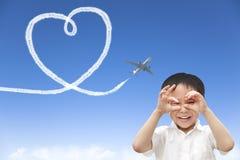 Flugzeugfliegen und -zeichnung des glücklichen Jungen aufpassendes ein Herz der Wolke Stockfotos