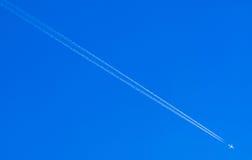 Flugzeugkondensstreifen, der unten auf blauen Himmel geht Stockfotos