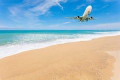 Flugzeuglandung über schönem Strand- und Seehintergrund Stockbild