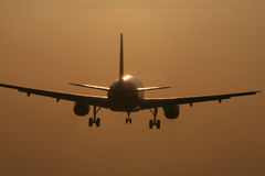 Flugzeuglandung im Sonnenuntergang Lizenzfreie Stockfotos