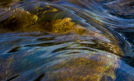 Fluid Color. River water flowing over submerged rock Royalty Free Stock Photography
