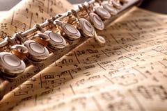 Fluit en oude bladmuziek op zwarte lijstvoorzijde opgeheven mening royalty-vrije stock afbeeldingen