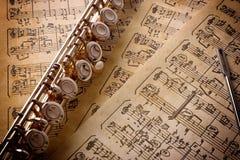 Fluit met staaf op oude met de hand geschreven bladmuziek opgeheven mening Stock Afbeelding