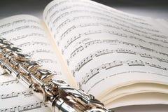 Fluit op een open muzikale score met grijze achtergrond Stock Foto