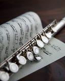 Fluit op muzikale score Stock Afbeelding