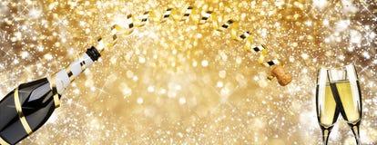 Fluiten van de de toostchampagne van de nieuw jaar de 'vooravond, gouden lint en de gouden achtergrond van de vuurwerkfonkeling royalty-vrije stock foto