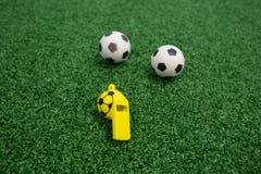 Fluitje en voetballen op kunstmatig gras Royalty-vrije Stock Afbeeldingen