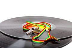 Fluitje met gestreept koord op vinylverslagen, witte achtergrond met exemplaarruimte stock fotografie