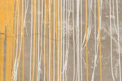 Flujo amarillo y blanco abstracto de la pintura del color abajo en la pared Fotos de archivo