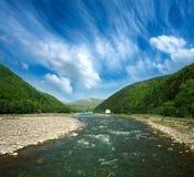 Flujo del río entre las montañas del bosque en el cielo dramático Imagenes de archivo