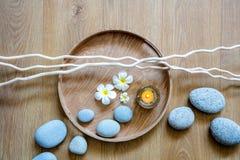 Flujo del zen de guijarros, de vela, de flores y de ramitas sobre la madera Imagen de archivo