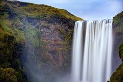 Flujo liso en la cascada de Skogafoss Foto de archivo libre de regalías