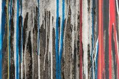 Flujo rojo y azul abstracto de la pintura del color abajo en la pared negra Imagenes de archivo