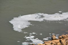 Flujos de las aguas residuales en el río foto de archivo