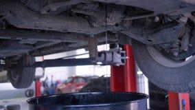 Flujos del aceite del automóvil en el cubo del coche aumentado en la elevación en la gasolinera almacen de video