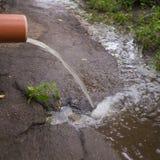 Flujos del agua de lluvia del tubo de drenaje de un edificio alto fotografía de archivo