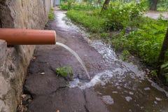 Flujos del agua de lluvia del tubo de drenaje de un edificio alto foto de archivo
