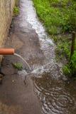Flujos del agua de lluvia del tubo de drenaje de un edificio alto fotos de archivo