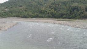 Flujos del río de la montaña sobre las piedras metrajes