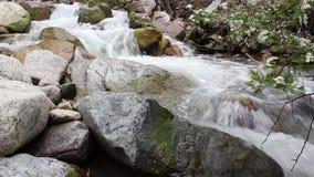 Flujos ?speros del r?o de la monta?a entre piedras grandes metrajes
