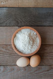 Fluor with two eggs. Flour with two eggs on wooden table Stock Photos